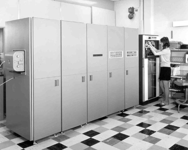 Hardcopy Camera on the SC4020, showing a computer the size of 5 refrigerators side by side being operated by a woman.