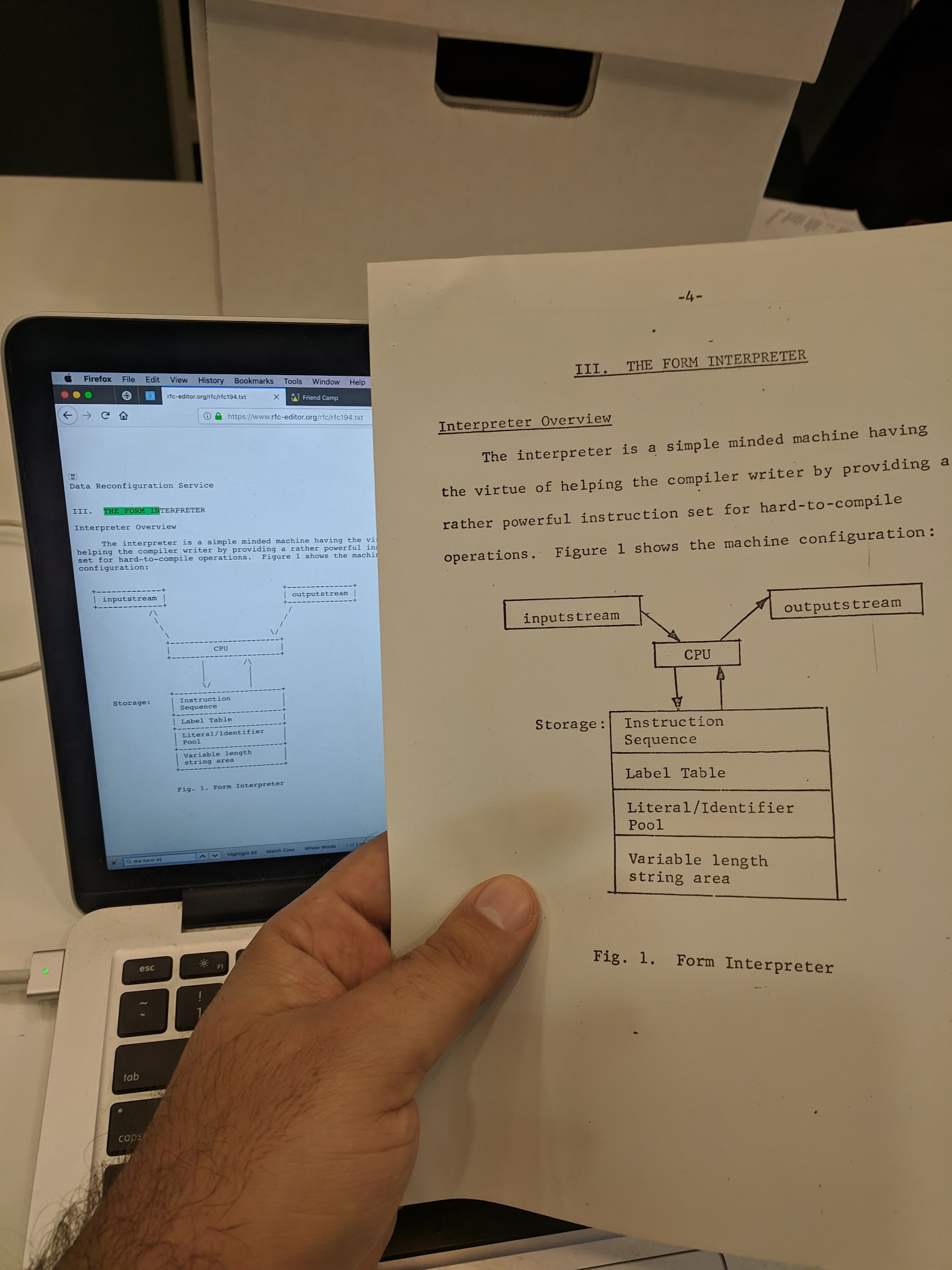 Photo of a paper document held next a computer monitor, showing the discrepancy described above.