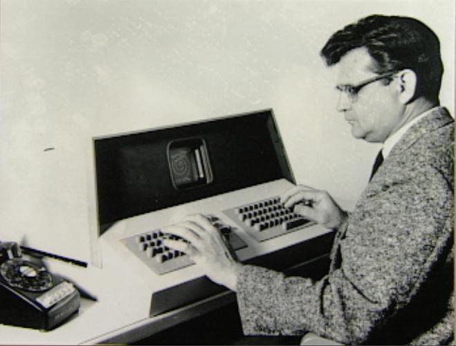 Glenn Culler sitting at an OLS terminal, looking at a very small screen and using a dual keyboard.