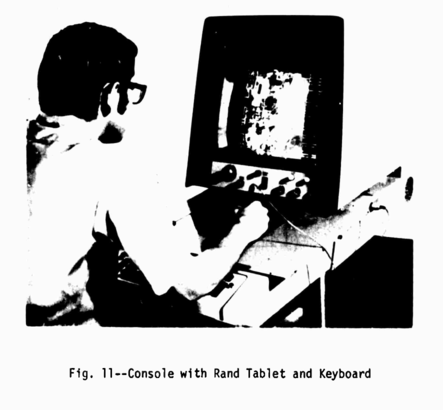 A blurry black and white image of a man hunched over an electronic tablet, looking at a monitor with a bunch of knobs and dials on it.