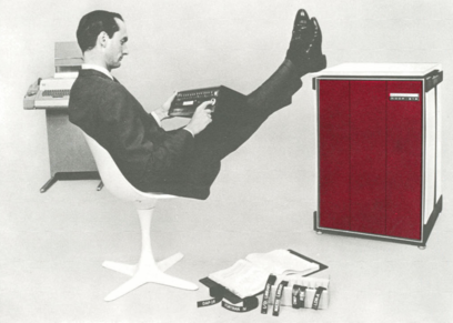 A man in a suit reclining in a space age chair with his feet up on the Honeywell DDP-516.